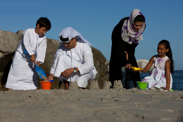 Arab family making sandcastle on beach --- Image by © Patrick Eckersley/arabianEye/Corbis